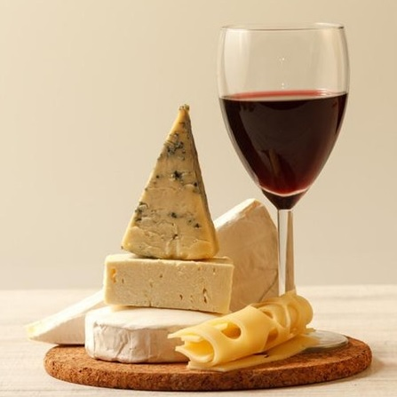 An image of a cheeseboard and a glass of wine